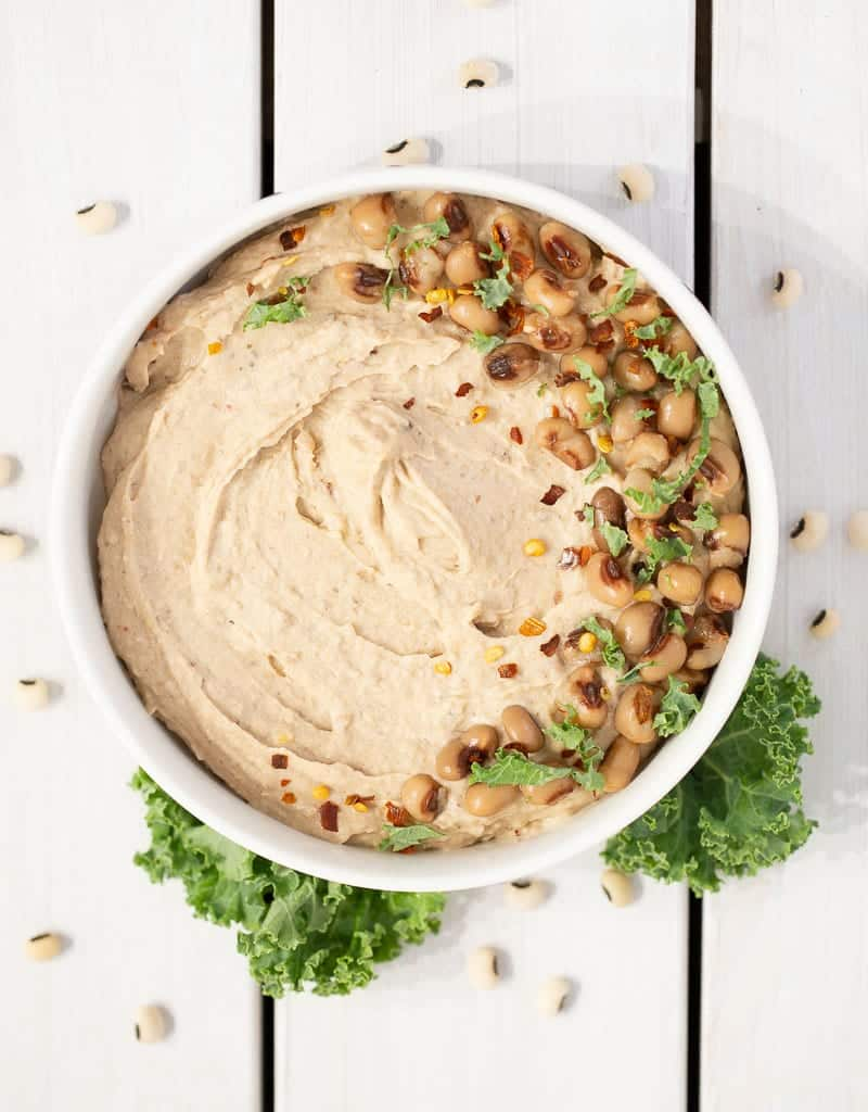 black eyed pea hummus in a bowl with toppings