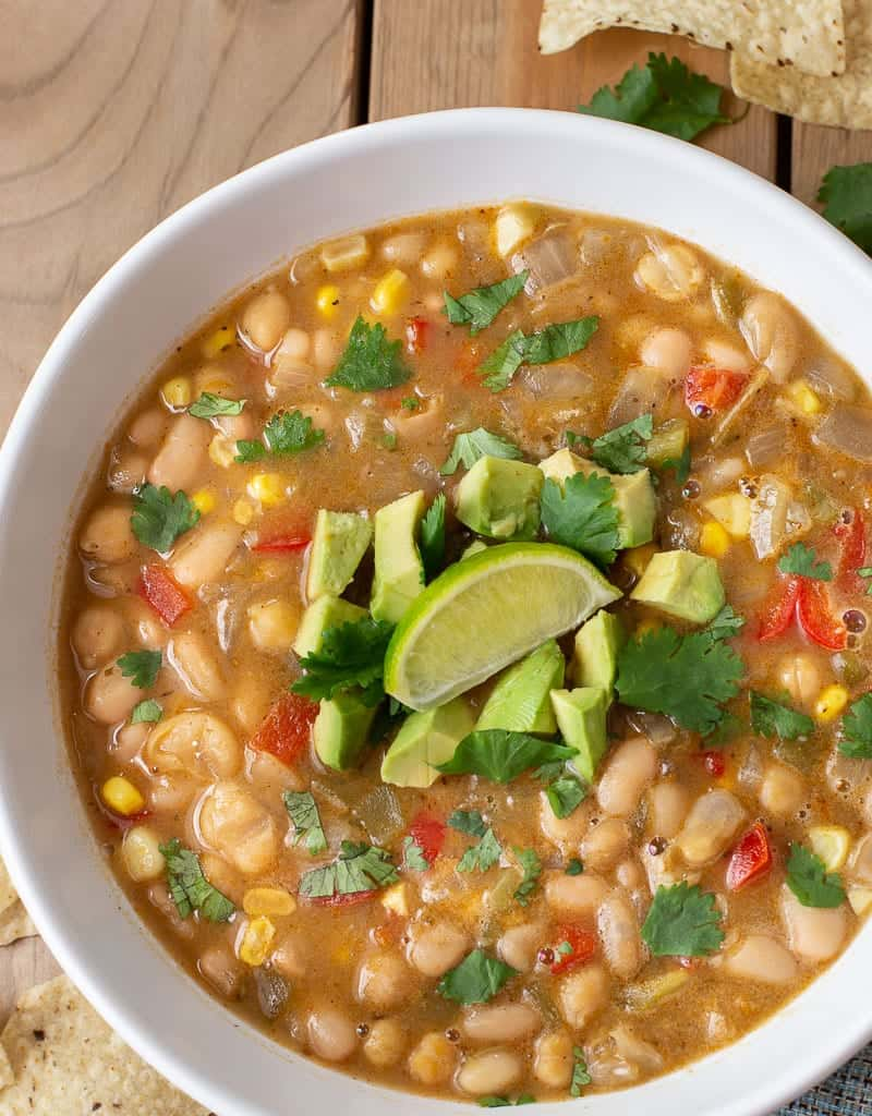 vegan white bean chili in a bowl topped with cilantro and lime