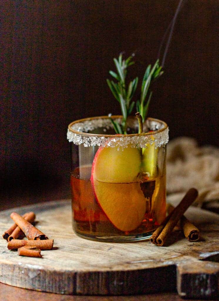 apple cider mocktail with slice of apple in it and rosemary lite on fire